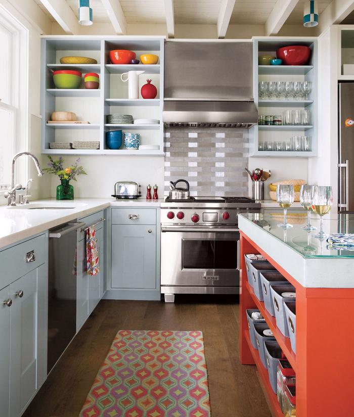 une cuisine grise et blanche aux accents pop équipée d'un îlot central orange avec espace rangement à comptoir en verre