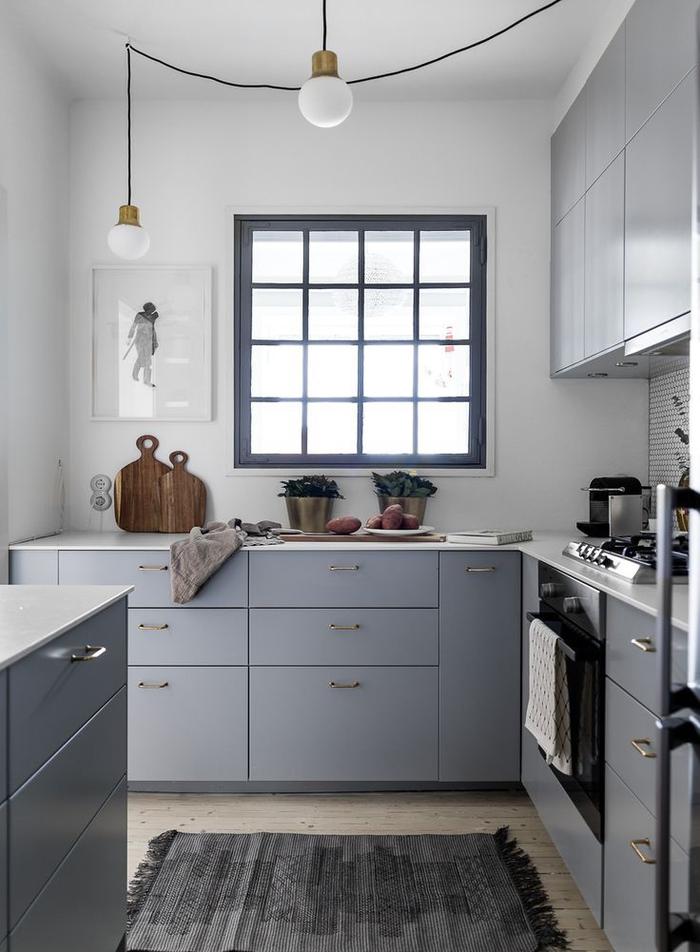 une cuisine gris clair de petite surface, de style scandinave épuré avec des murs blanc et parquet en bois clair