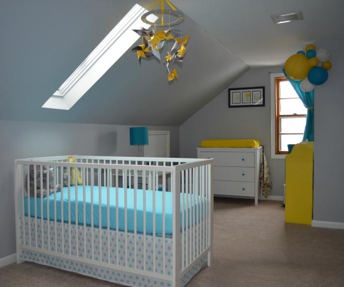 chambre sous pente aux murs blancs avec meubles blancs et accents vibrants jaune et bleu, mobile bébé jaune et gris