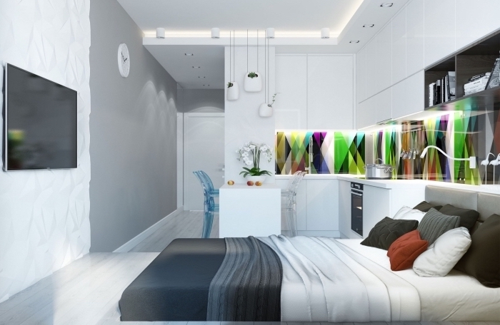exemple d'intérieur moderne dans un petit studio étudiant ou célibataire aux murs blancs avec crédence multicolore dans la cuisine