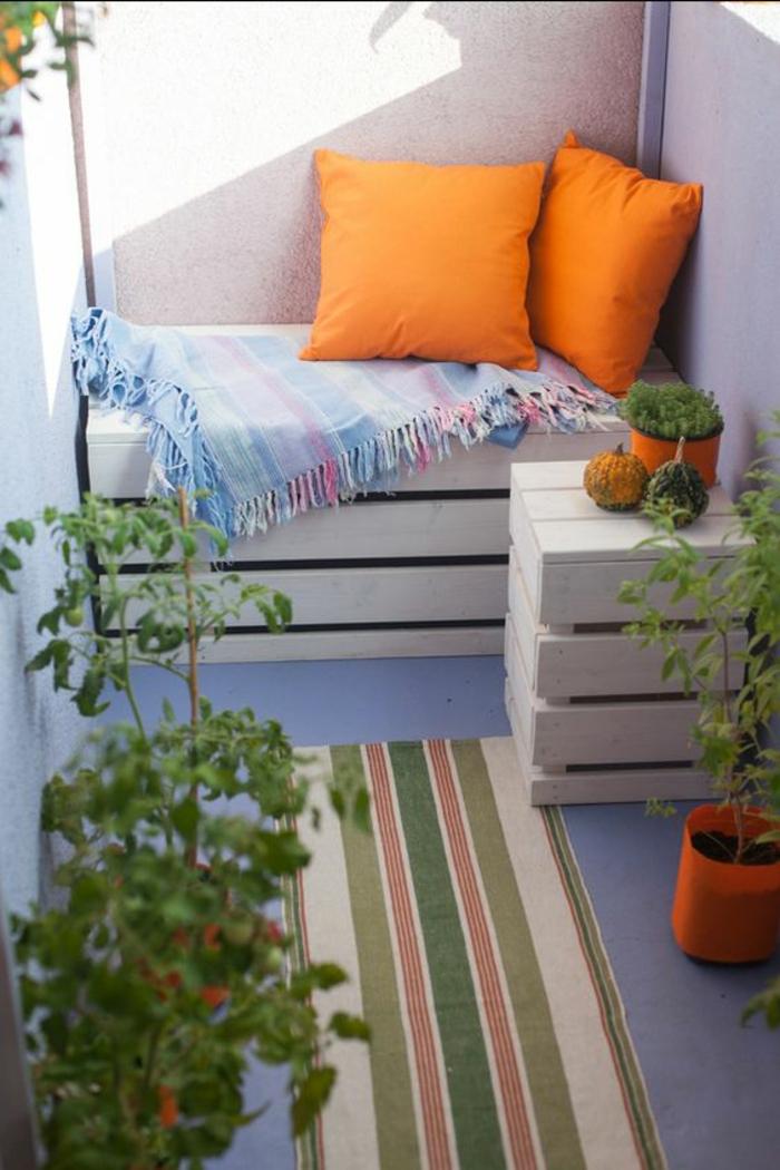 idee deco terrasse, balcon fleuri, palettes transformées en meubles, banc deux places et petite table avec petit pot plante verte, tapis en style ethnique