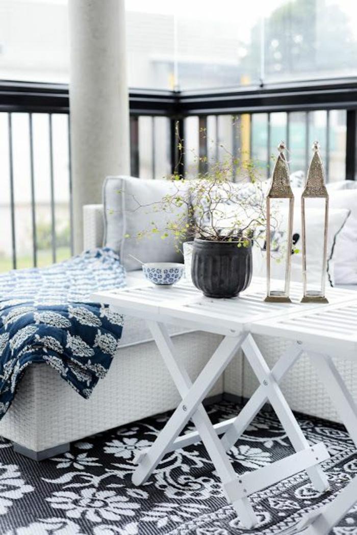 idee deco terrasse, aménagement terrasse appartement, canapé d'angle en rotin blanc, tapis en noir et blanc avec des motifs fleuris, tables basses en bois PVC blanc