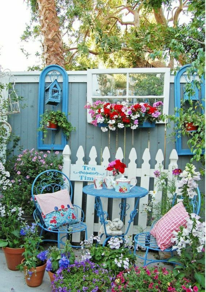 idee amenagement jardin devant maison, amenagement jardin paysager, une petite partie de cintre en bois blanc comme déco, deux chaises en métal bleu et une table ronde, coussins aux carreaux blancs et rouges