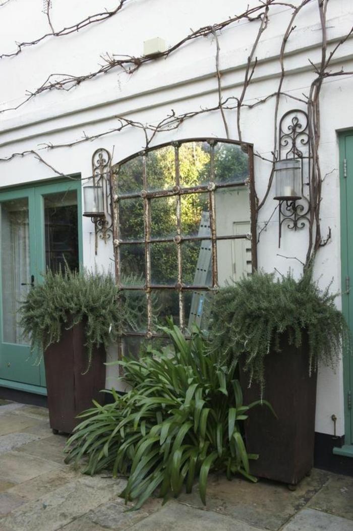 idee amenagement jardin devant maison, grand miroir vintage monté au mur, deux grands pots noirs en forme carrée des deux cotés du miroir, deux luminaires lanternes style années 50