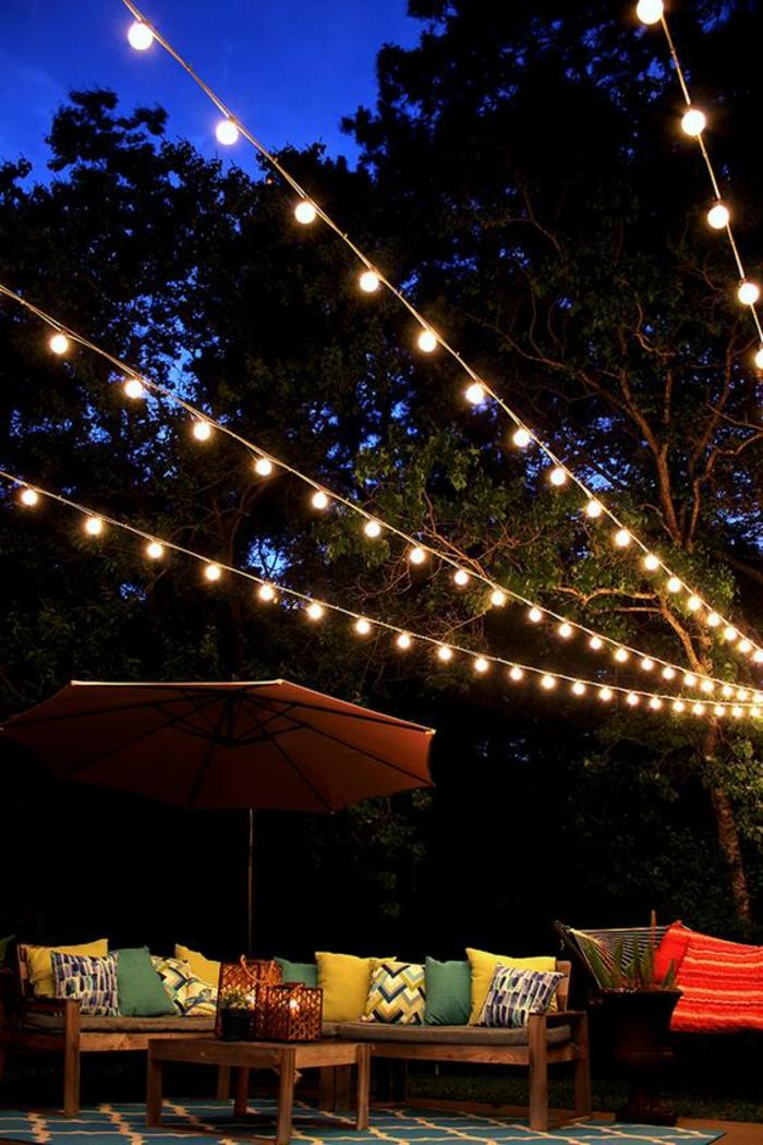 deco jardin pas cher avec des guirlandes sur les arbres, coin causette avec des meubles de jardin et des coussins en vert et jaune et motifs grahiques