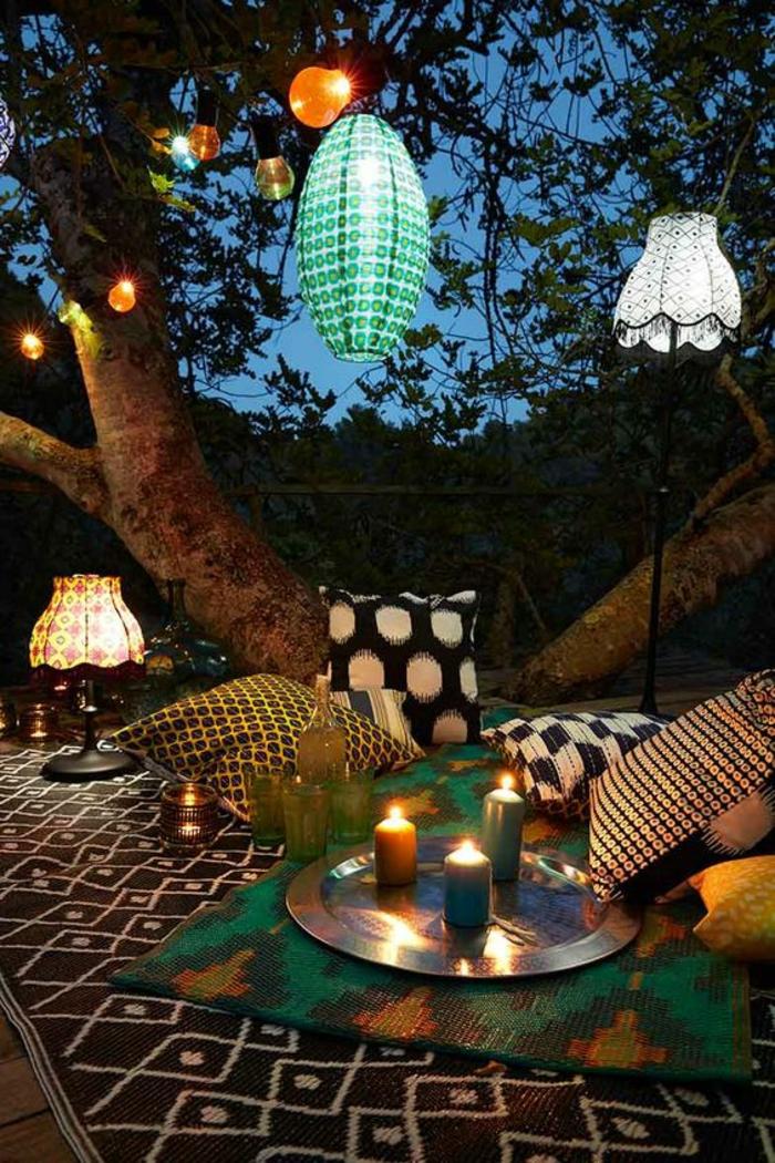 amenagement exterieur en style bohème, lanternes en formes et couleurs différentes accrochées aux branches d'un arbre, tapis oriental parsemé de coussins aux pois, luminaire avec abat-jour classique posé par terre