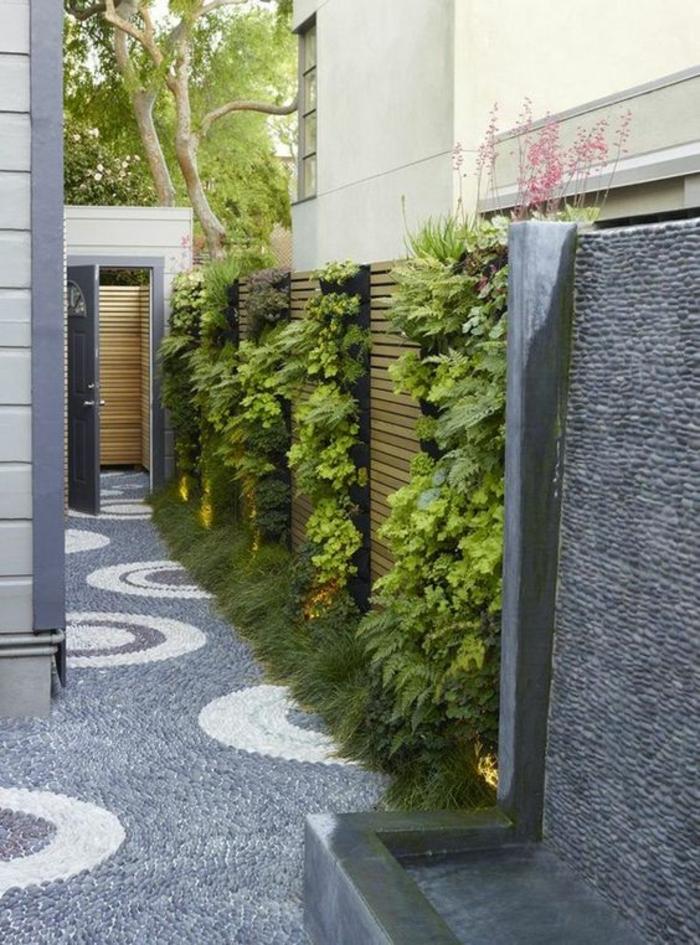 decorer son jardin en le rendant moderne, plantes vertes, et murs recouverts de revêtements muraux gris en pierres minuscules, sol recouvert de motifs en cercles blancs