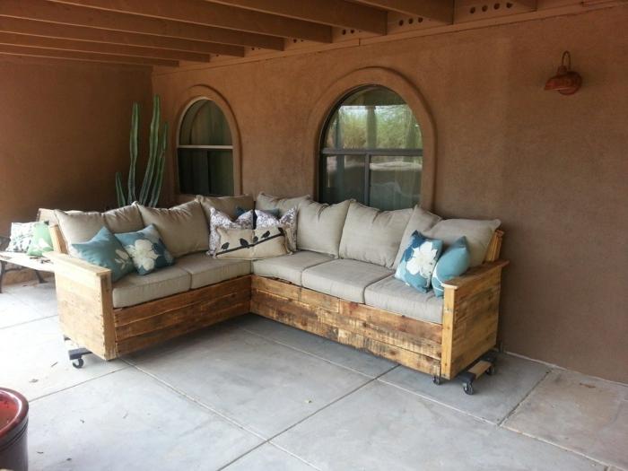 style d'aménagement mexicain hacienda, canapé palette, coussins en couleur ivoire, coussins en bleu pastel et blanc, meuble avec des roues