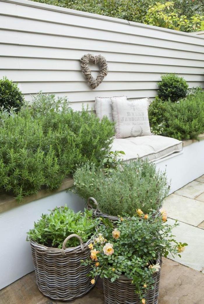 canapé de jardin recouvert de coussins en blanc, cintre couleur crème décoré avec un grand cœur en rotin tressé, jardin deco, décorer son jardin
