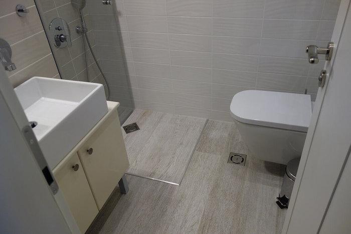 mini salle de bain avec lavabo toilettes et douche italienne dans le coin