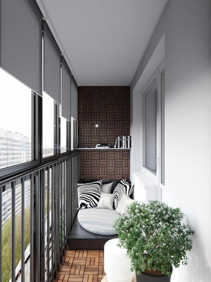 terrasse au sol en terre cuite avec un mur recouvert de panneau en bois dans les mêmes nuances, idee amenagement terrasse, matelas en simili cuir noir posé dans l'un des bouts, grands coussins aux prints zèbre, petits coussins blancs