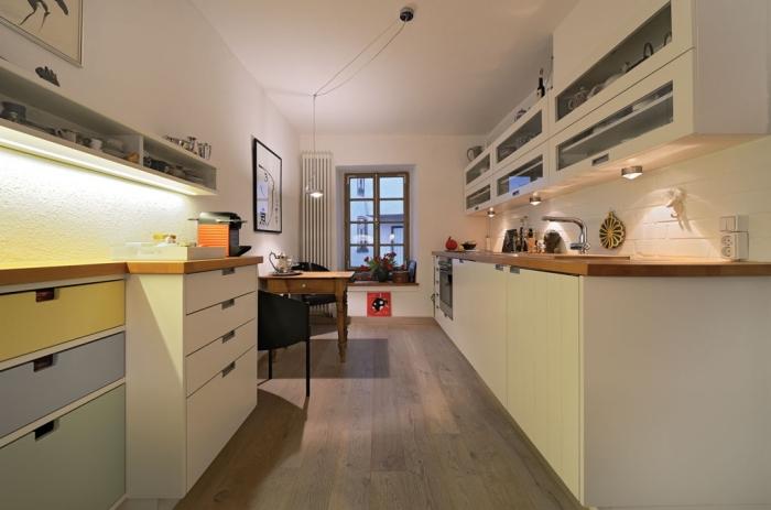 quel éclairage choisir pour aménager une cuisine en longueur aux murs blancs et plancher de bois stratifié foncé