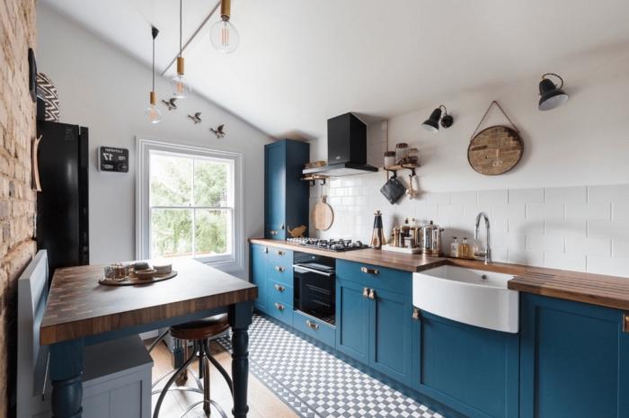 exemple de déco chic dans une cuisine aménagée en longueur avec pan de mur en briques rouges et plafond blanc