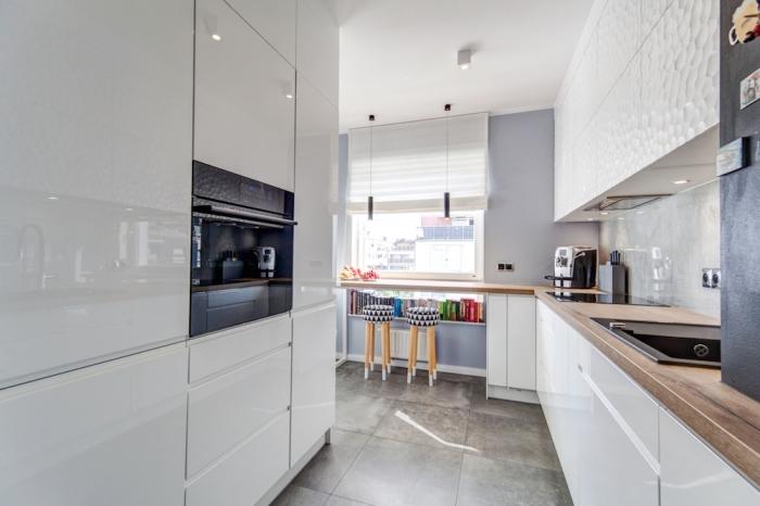 modèle de cuisine laquée blanche aménagée en L avec meubles blancs et bois sur carrelage de sol en gris clair