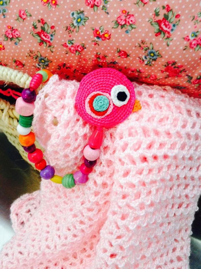 un accroche tetine girly au design unique réalisé avec des perles en silicone multicolores de taille et de forme variée et une tête d'oiseau au crochet