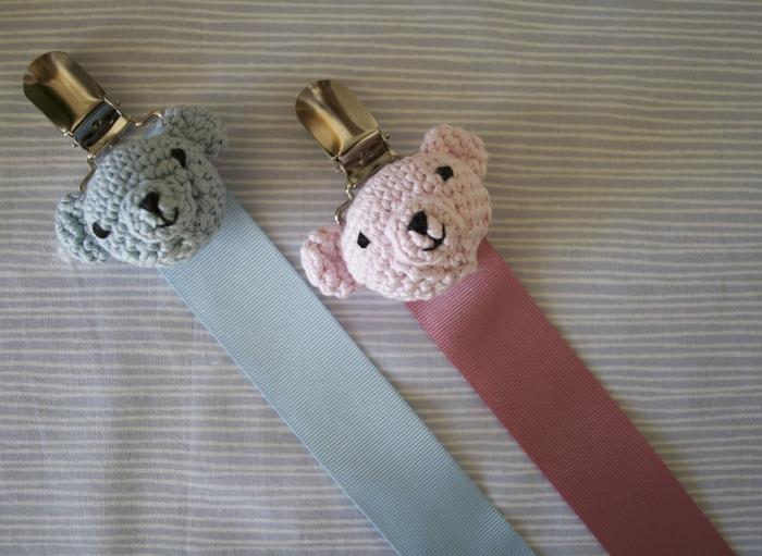 une pince clip attache tetine en métal qui permet de fixer la sucette sur le vêtements de bébé, modèle d'attache sucette décoré avec une tête d'ourson au crochet