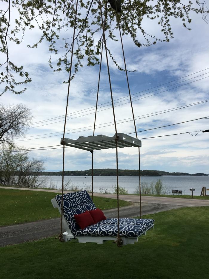 canapé balançoire suspendu avec des cordes sur les branches d'un arbre, palettes peintes en blanc, canapé en palette, meubles de jardin en palettes recouverts de matelas en bleu marine et blanc
