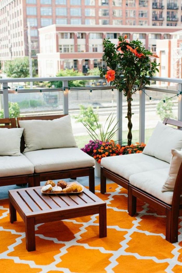 une idée déco terrasse, des meubles massifs en bois foncé en style asiatique avec table basse carrée, un arbre oranger fleuri, tapis en orange et blanc