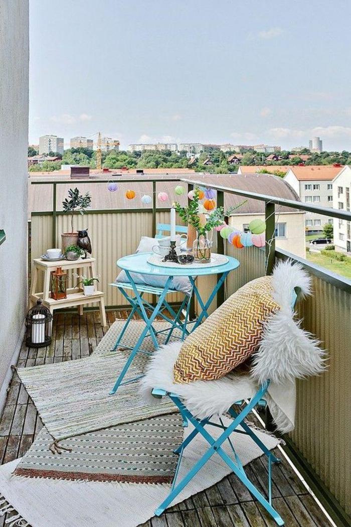 idée déco appartement, balcon décoré avec guirlande lumineuse avc boules colorées, trois tapis au sol de taille diverse en réséda et ivoire, deux chaises en métal bleu pastel pliables, table ronde et haute en métal bleu pastel