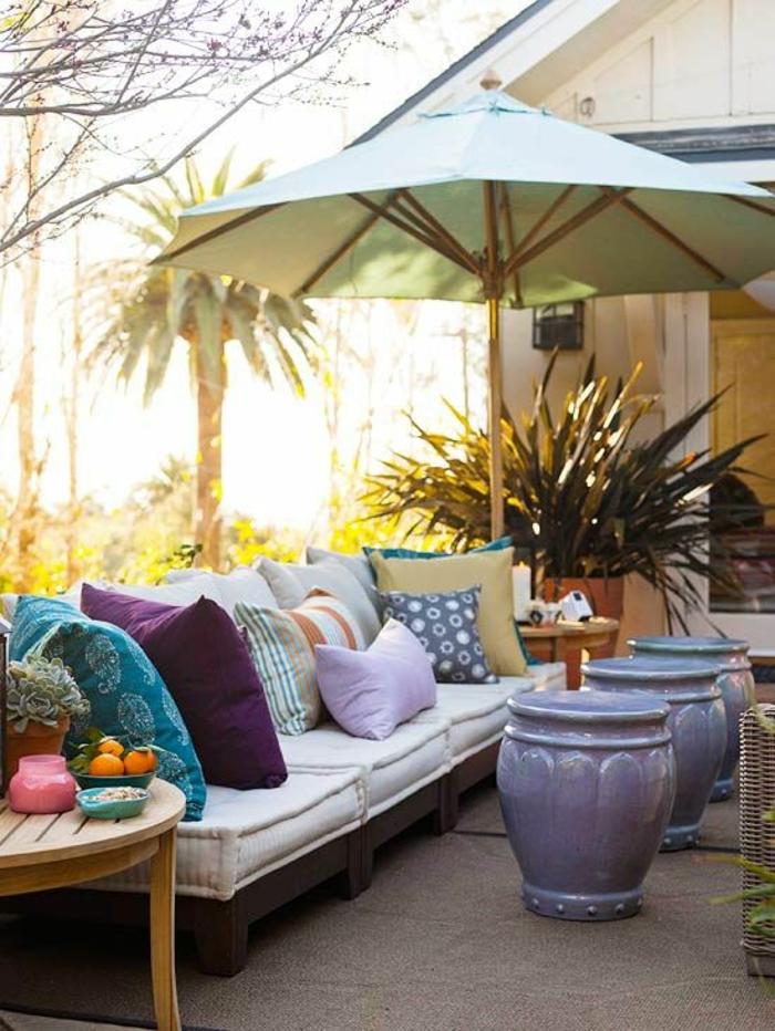 grand parasol en vert menthe, canapé en noir avec des coussins grands et petits dans toutes les couleurs, idee deco terrasse, trois pots en céramique bleu indigo, table ronde en bois