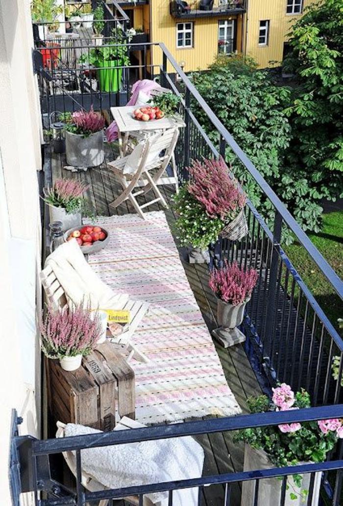 decoration jardin terrasse, decoration terrasse exterieur, garde-corps en métal bleu marine, tapis rectangulaire en rose et blanc, pots avec des branches de lavande, table métal blanc