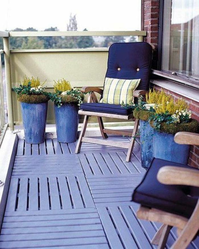 idée déco appartement, balcon fleuri, idee amenagement terrasse, sol recouvert de bois de palettes coloré en bleu marine, fauteuils de relax aux coussins en bleu marine, pots en bleu marine