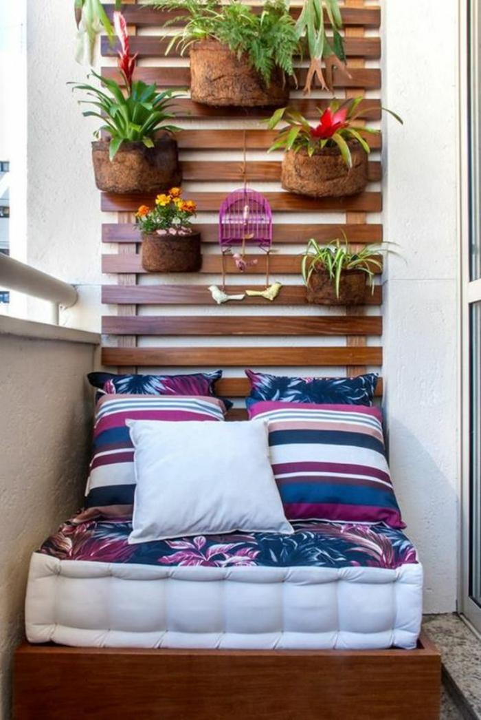 idee deco terrasse, fauteuil deux places, réalisé avec matelas et deux coussins pour le dossier en bleu marin et blanc avec du fuchsia, mur végétal en bois marron avec des pots marrons