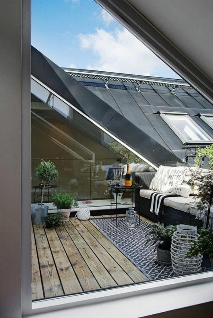 terrasse sous les combles, sur un toit de Paris, idée déco terrasse, tapis rectangulaire en noir et blanc, sol recouvert de poutres de bois clair, canapé jardin en noir avec des coussins en ivoire, pots avec des plantes vertes