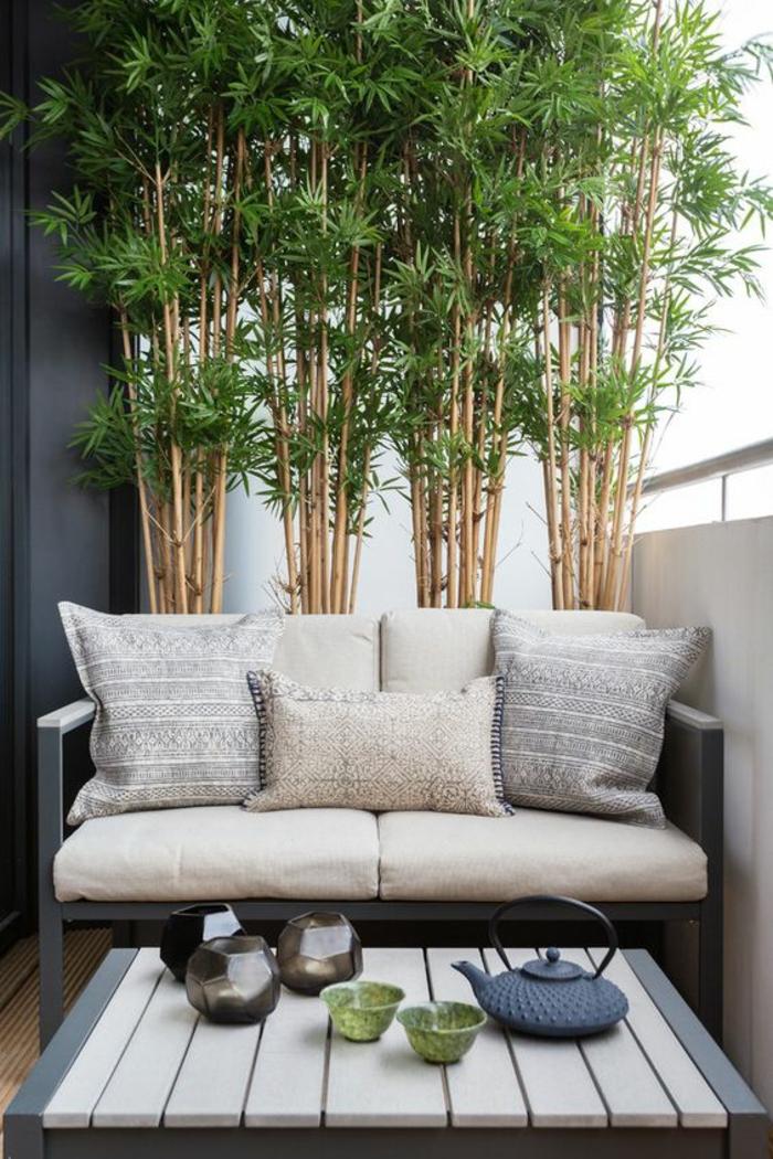 séparateur d'espace bambou, canapé en métal gris pastel rempli de coussins petits et grands, table basse avec plan en bois PVC blanc, accessoires pour le thé en style asiatique, idee deco terrasse