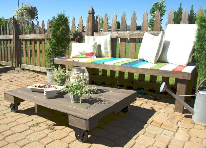 banquette en palette avec assise de diverses couleurs et coussins décoratifs, table basse palette facile à fabriquer