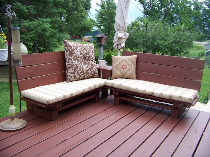 banquette palette de bois repeinte en marron avec des coussins d assise beige et marron sur une terrasse exterieure en bois