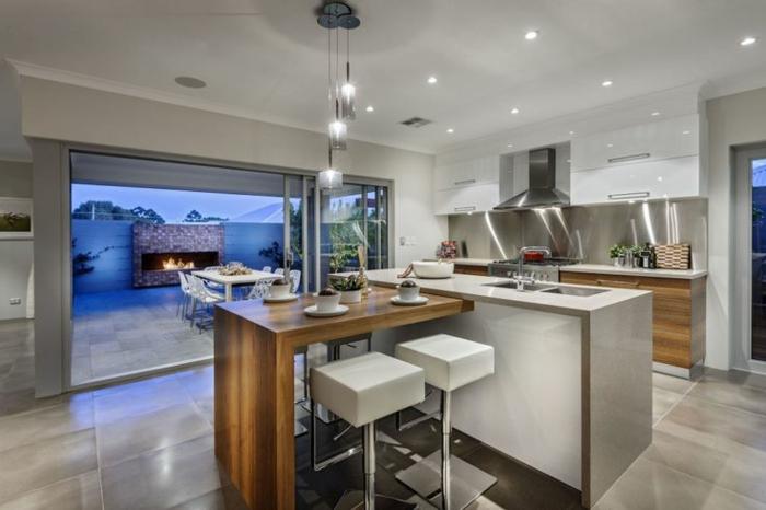 îlot central table dans une cuisine moderne, maison plain pied, cheminée à l'extérieur, cuisine en gris et blanc