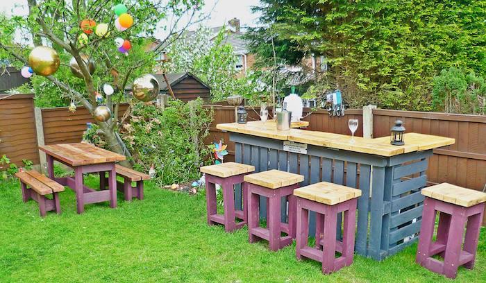 comment faire un bar en palette de bois avec bancs, table basse et tabourets mauve sur gazon dans un jardin
