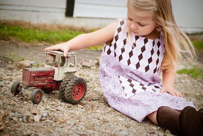 Photo coupe de cheveux petite fille coiffure petite fille adorable blonde fille mignonne qui joue avec un tracteur