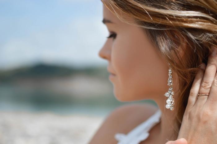 jeune fille aux cheveux raids éclaircis avec la technique balayage blond sur base châtain, modèle de boucles d'oreilles en perles