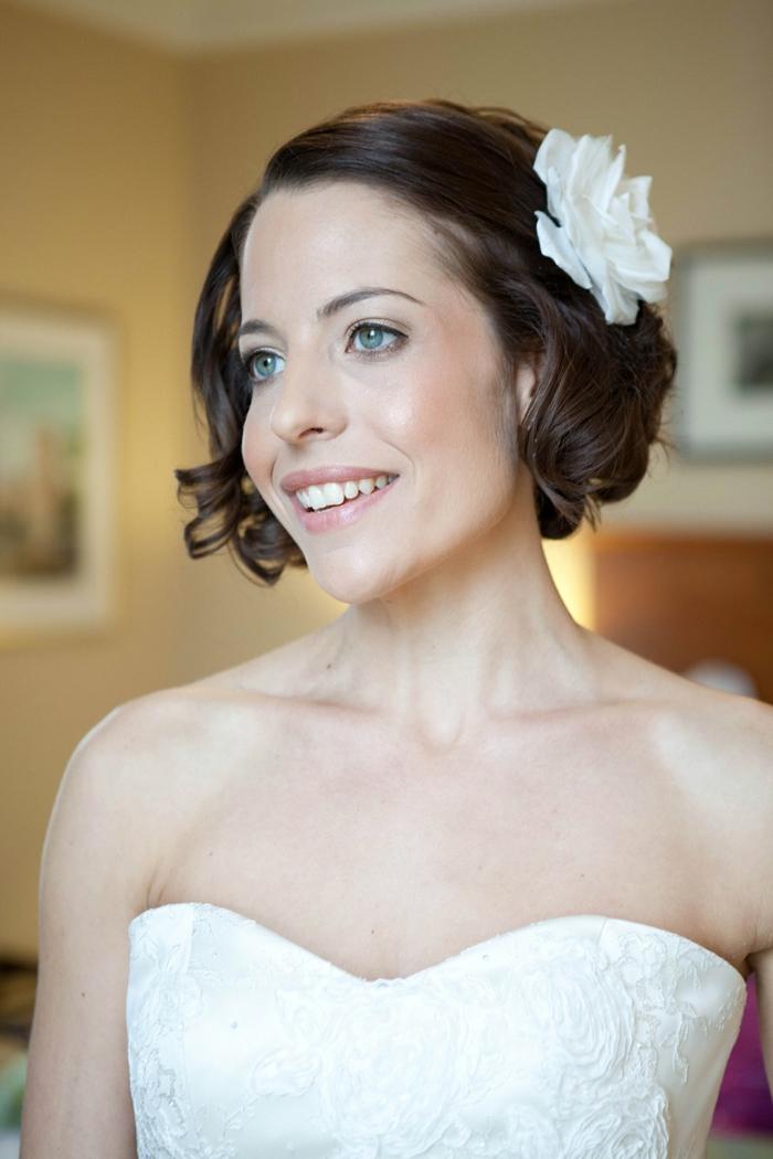 mariée avec coupe au carré, grande fleur en tissu blanche, raie latérale, ondulations légères sur les cotés, maquillage naturel, sourcils légèrement soulignes au crayon noisette, coiffure mariage cheveux courts