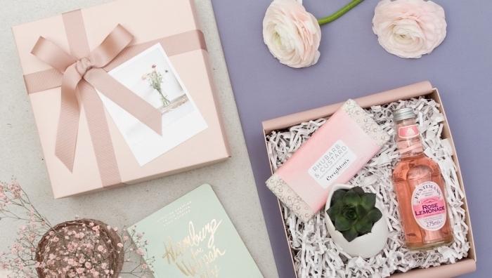 collection de produits cosmétiques et décoratifs dans une boîte cadeau à emballage diy en papier rose pastel avec ruban