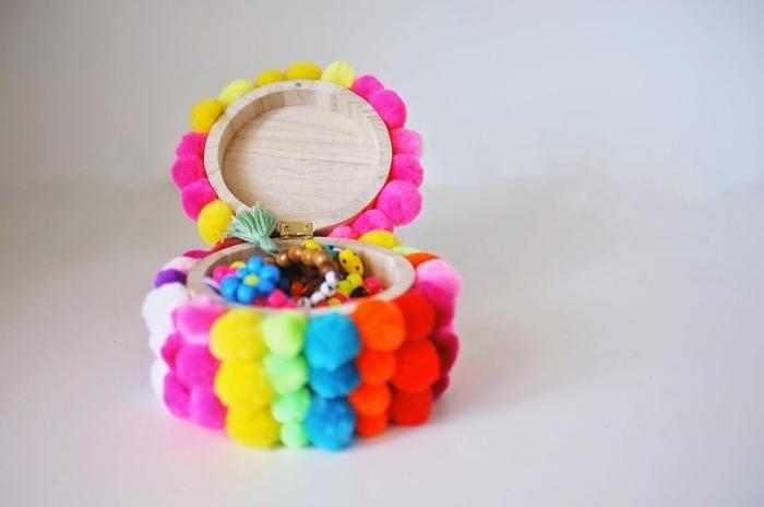 objet décoratif en forme de mini boîte à bijoux de bois clair couverte de petits pompons en couleurs variées