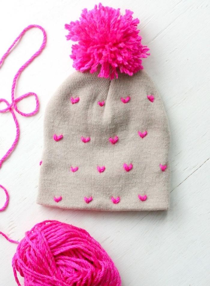 activité manuelle maternelle pour customiser un bonnet beige avec déco en fil rose en formes de coeur et pompons rose fuschia