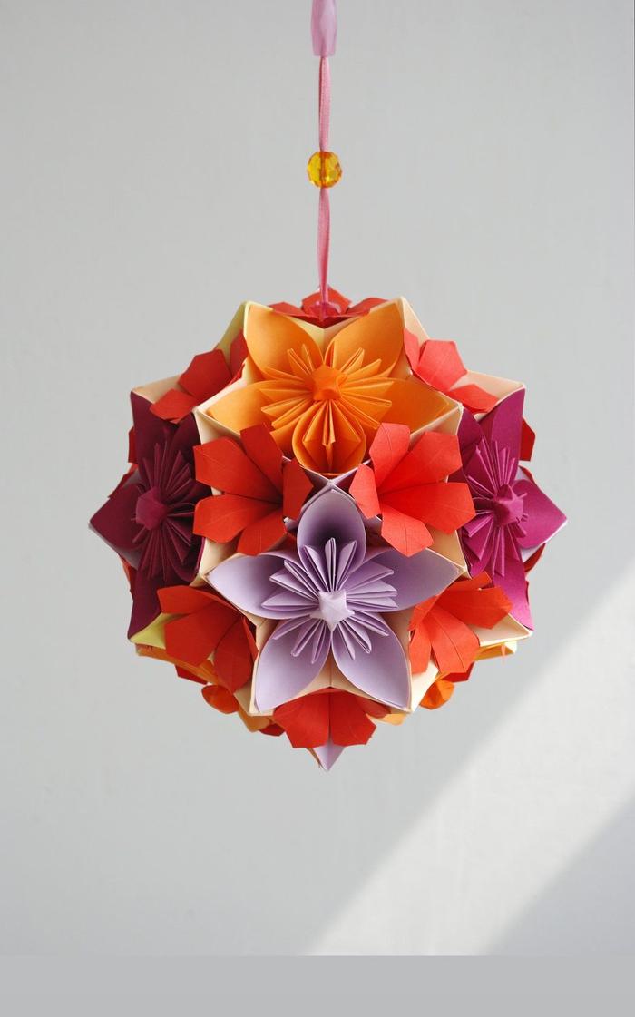 une boule kusudama multicolore composées de fleurs en origami collées ensemble, modele origami d'une fleur traditionnelle pour l'art de pliage origami japonais