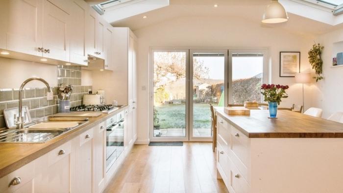 exemple de cuisine blanche avec crédence grise et comptoir en bois clair équipée d'un meuble cuisine plan de travail en bois