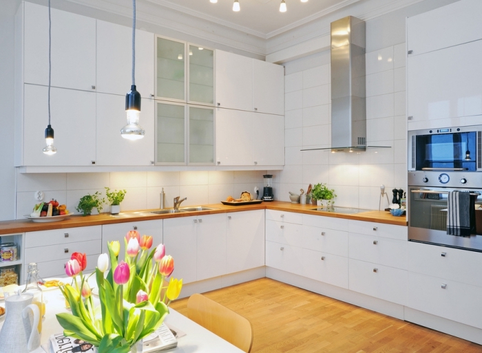 aménagement d'une cuisine d'angle avec armoires blanches et en verre combinés avec plan de travail stratifié