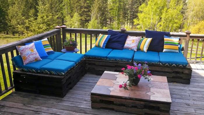 canapé en palette avec des palettes recyclées bois brut marron coussins d assise bleues, table basse palette avec revêtement de carreaux