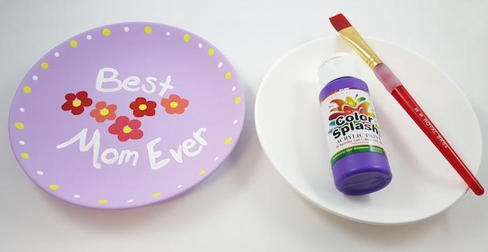 idée de bricolage fête des mères maternelle avec une assiette blanche customisée de peinture violette, fleurs colorés et les mots meilleur maman au monde