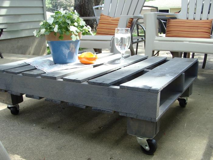 exemple de table basse en palette facile à faire avec une palette repeinte en gris et roulettes montées, chaises de jardin