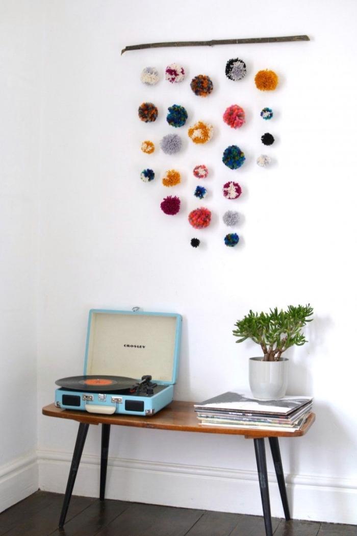 idée décoration d'une pièce aux murs blancs et parquet noir avec suspension murale de style boho chic en pompons de laine