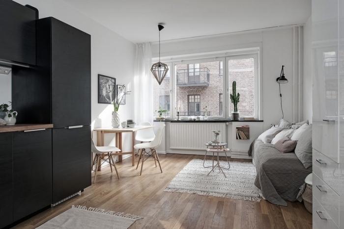 petite cuisine équipée avec meubles en noir mate et poignées métalliques combinés avec plan de travail en bois massif foncé