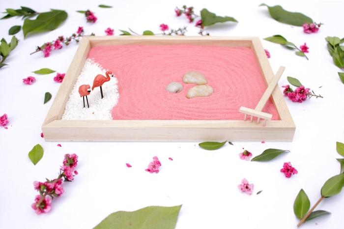 un jardin zen miniature avec un lit de sable rose, un mini rateau et des figurines flamants roses, idee cadeau fete des meres à faire soi-même
