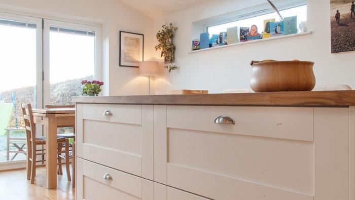 meuble cuisine avec plan de travail de bois foncé et armoires blanches aux poignées métalliques sur plancher de bois clair