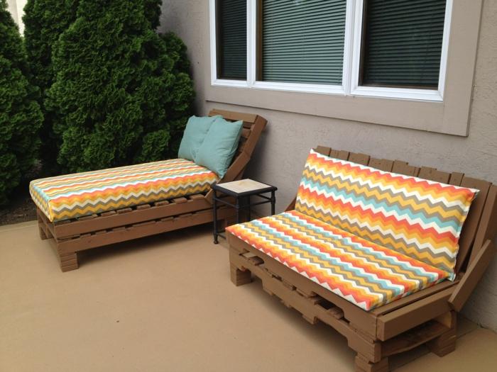 banc en palette, salon de jardin en palette, chaises-longues en bois peint en marron, matelas avec des motifs en couleurs oranges, bleu pastel, blanc et vert